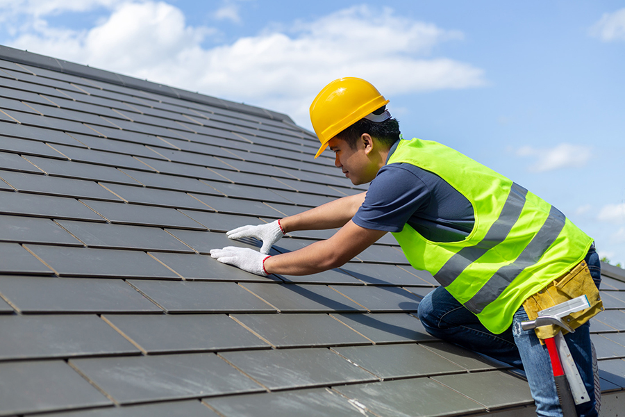 Roof repair, worker with white gloves replacing gray tiles or shingles on house with blue sky as background and copy space, Roofing - construction worker standing on a roof covering it with tiles.
